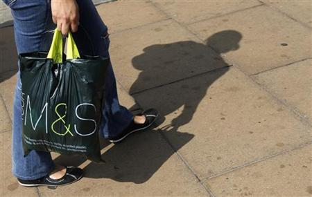 A shoppers carries a Marks and Spencer bag on Oxford Street in London May 25, 2010. REUTERS/Luke MacGregor
