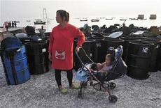 <p>A woman stands with her child next to containers filled with oil cleaned up from the oil spill site at a port in Dalian, Liaoning province July 25, 2010. REUTERS/Stringer</p>