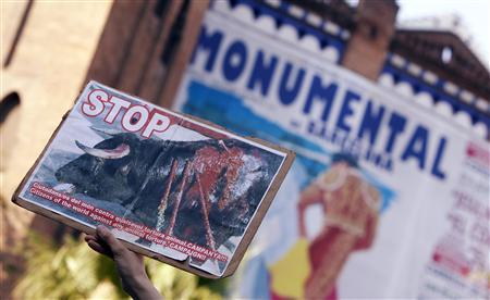 A woman holds a banner as she protests against bullfighting outside Barcelona's bullring before a festival in Barcelona July 25, 2010. REUTERS/Sergio Perez