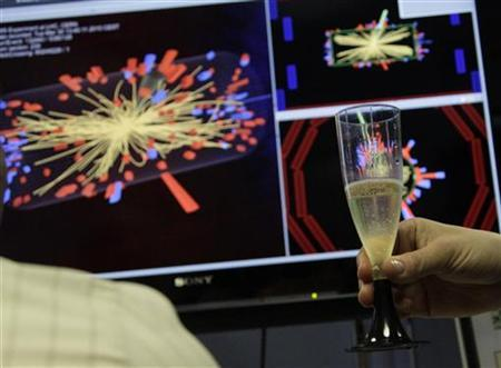 A scientist holds a glass of champagne after the first successful collisions at full power at the Compact Muon Solenoid (CMS) experience control room at the Large European Organisation for Nuclear Research (CERN) in Meyrin, near Geneva, March 30, 2010. REUTERS/Denis Balibouse