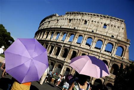 Tourists use umbrellas to shade themselves from the sun as they visit Rome's ancient Colosseum during a hot summer day in Rome July 21, 2010. REUTERS/Alessia Pierdomenico (
