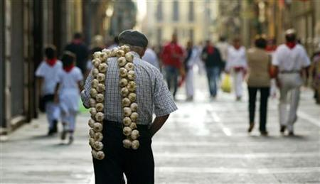 A man carries a string of garlic on his shoulder through the old part of town during San Fermin Festival in Pamplona July 10, 2006. REUTERS/Pablo Sanchez