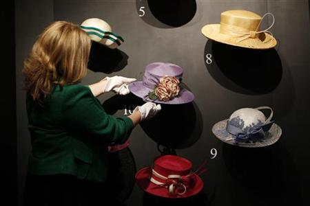 A curator poses for photographs with a collection of hats worn to Royal Ascot by the Queen, at Buckingham Palace in London July 23, 2010. REUTERS/Suzanne Plunkett