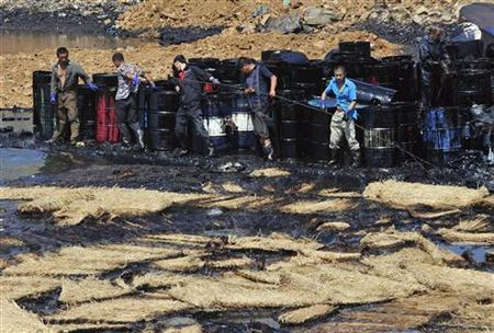 Workers clean up oil at an oil spill site near Dalian Port, Liaoning province July 27, 2010. Nearly 8,000 workers and hundreds of fishing boats have managed to clean up the oil spill off the major northern Chinese port Dalian, nine days after a pipeline blast leaked 1,500 tonnes of heavy crude into the sea. REUTERS/Stringer