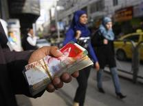 <p>Palestinian women walk past a money changer in the West Bank city of Ramallah February 16, 2010. REUTERS/Mohamad Torokman</p>