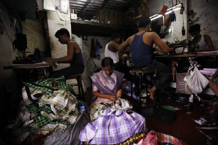 Fifteen-year-old Saira (C) cuts shirt threads inside a garment factory in Mumbai August 3, 2010. REUTERS/Danish Siddiqui