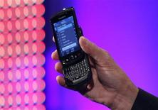 <p>AT&T Mobility Chief Executive Ralph de la Vega holds the new BlackBerry Torch 9800 smartphone at a news conference in New York August 3, 2010. REUTERS/Shannon Stapleton</p>