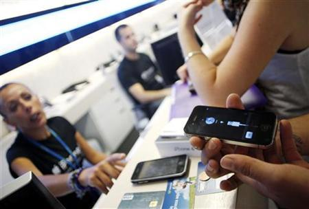 A customer checks his new iPhone 4 at a Telefonica store in Madrid July 30, 2010. REUTERS/Susana Vera