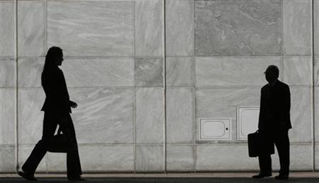 People are silhouetted at Canary Wharf business district in London in a file photo. REUTERS/Luke MacGregor