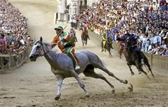 <p>Silvano Mulas (L) of Selva parish leads the pack of horses to win the Palio race in Siena July 2, 2010. REUTERS/Marco Bucco</p>
