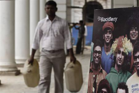 A man carries empty water containers as he walks past a Blackberry billboard in New Delhi August 12, 2010. REUTERS/Adnan Abidi