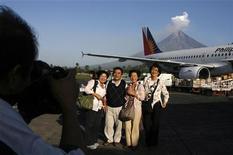<p>Touristes japonais sur le tarmac de l'aéroport indonésien de Legazpi City, avec le volcan Mayon en arrière plan. Seulement deux-tiers des salariés dans le monde utilisent la totalité des jours de vacances qui leur sont accordés, révèle un sondage Reuters-Ipsos. Les Japonais sont particulièrement réticents à l'idée de profiter pleinement de leur temps de loisir, seuls 33% d'entre eux exerçant ce droit tandis que les Franais en profitent pour 89% d'entre eux. /Photo d'archives/REUTERS/Erik de Castro</p>