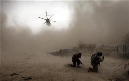 Soldiers with the U.S. Army's 1-320 Field Artillery Regiment, 101st Airborne Division shield themselves from the dust as a Medivac helicopter takes off outside Combat Outpost Nolen in the Arghandab Valley north of Kandahar July 30, 2010. REUTERS/Bob Strong
