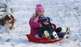 <p>Youngsters toboggan in the snow, in Princes Risborough, southern England January 5, 2009. REUTERS/Eddie Keogh</p>
