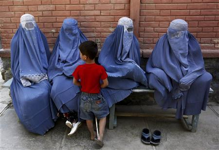 Afghan women and a child wait for transport in Kabul, August 24, 2010. REUTERS/ Omar Sobhani