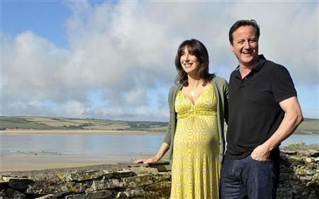 Britain's Prime Minister David Cameron, and his wife Samantha, pose for a photograph on the coastal path at Daymer Bay in Cornwall, August 22, 2010 REUTERS/Ben Birchall/Pool