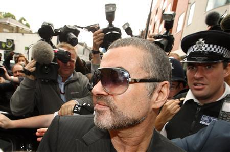 George Michael is escorted out of Highbury Corner Magistrates Court in London, August 24, 2010. REUTERS/Andrew Winning