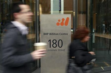 Pedestrians walk past the head office of BHP Billiton in central Melbourne August 18, 2010. REUTERS/Mick Tsikas