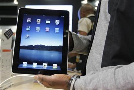 A salesman displays an Apple iPad during its launch in Brussels July 23, 2010. The iPad became available to the public through Apple retailers in Belgium on Friday. REUTERS/Thierry Roge