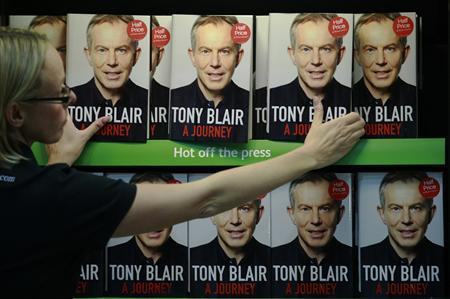 An employee poses with the political memoirs of Britain's former Prime Minister Tony Blair, ''A Journey'', in a bookshop in London, September 1, 2010. REUTERS/Luke MacGregor