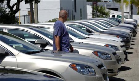 A man walks next to Chevrolet vehicles at a GM dealership in Miami, Florida August 12, 2010. REUTERS/Carlos Barria