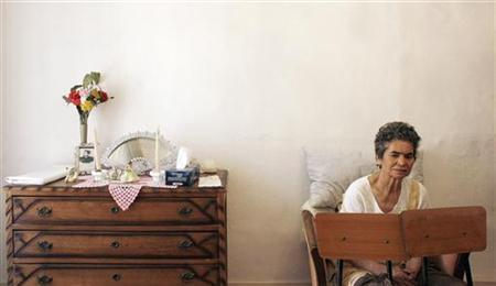 Alzheimer's disease patient Isidora Tomaz, 82, sits in her armchair with two chairs placed in front of her by her husband Amilcar Dos Santos (unseen) to prevent her from falling to the ground in their house in Lisbon September 15, 2009. REUTERS/Nacho Doce