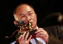<p>Director John Woo poses after he received a Golden Lion for Lifetime Achievement during the closing ceremony of the 66th Venice Film Festival September 3, 2010. REUTERS/Alessandro Bianchi</p>