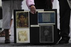 <p>Relatives of Guatemalan farmers murdered in 1982 show a poster during the start of the trial of former soldiers Manuel Popsun, Reyes Gualip and Carlos Carias outside the justice courts in Guatemala City, September 8, 2010. REUTERS/Edgard Garrido</p>