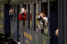 <p>Passengers riding in a steam train of the Dampfbahn Furka Bergstrecke (DFB) railways take pictures near the village of Gletsch August 27, 2010. REUTERS/Arnd Wiegmann</p>