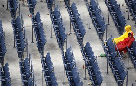 Fans sit in the rain in Arthur Ashe Stadium during a rain delay at the U.S. Open tennis tournament in New York, September 12, 2010. REUTERS/Jessica Rinaldi