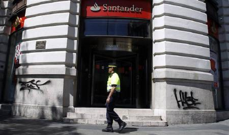 A local police officer walks past a branch of Eurozone biggest bank Santander in central Madrid, July 23, 2010. REUTERS/Sergio Perez/Files