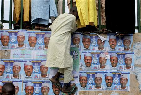 A boy tries to climb a wall pasted with election posters in Nigeria's northern city of Kano September 10, 2010. REUTERS/Akintunde Akinleye