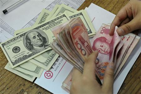 An employee counts Renminbi yuan banknotes next to U.S. dollars at a branch of Bank of China in Hefei, Anhui province September 15, 2010. REUTERS/Stringer
