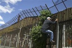 <p>Foto de archivo de una persona intentando trepar el muro fronterizo entre la localidad mexicana de Nogales y Arizona en Estados Unidos, mayo 1 2010. El plan de Estados Unidos para construir un muro en su frontera sur causó protestas en México y dividió a los estadounidenses cuando fue aprobado en una ley en el 2006, pero el tema quedó ensombrecido a raíz de la recesión económica del año pasado. REUTERS/Alonso Castillo</p>