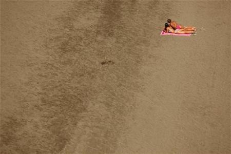 Women sunbath on the beach on a hot summer day in Rincon de la Victoria, near Malaga, southern Spain, August 27, 2010. REUTERS/Jon Nazca