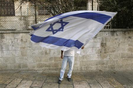 An Israeli settler waves a flag across the street from a left-wing protest in Jerusalem calling for the continuation of a building freeze September 26, 2010. REUTERS/Ammar Awad