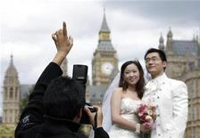 <p>A Chinese couple Yasmine Liu and Jeremy Sun pose for a wedding photo outside the Houses of Parliament in London August 19, 2010. REUTERS/Stefan Wermuth</p>