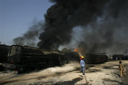 Firemen extinguish a fire on a burning oil tanker on a highway near Shikarpur, about 39 km (24 miles) from Sukkur in Pakistan's Sindh province, October 1, 2010. REUTERS/Athar Hussain