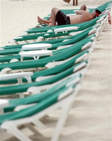 A tourist couple relax on beach chairs in Cancun April 13, 2010. REUTERS/Gerardo Garcia