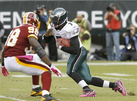 Philadelphia Eagles quarterback Michael Vick runs the ball under pressure from the Washington Redskins linebacker Brian Orakpo (98) during the first quarter of their NFL football game in Philadelphia, Pennsylvania, October 3, 2010. REUTERS/Tim Shaffer