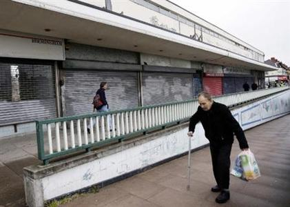 A man walks past closed shops in Birmingham, May 13, 2009. REUTERS/Darren Staples