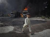 <p>A school boy, wearing a backpack, walks past burning fuel tankers along the GT road in Nowshera, located in Pakistan's Khyber-Pakhtunkhwa Province October 7, 2010. REUTERS/Adrees Latif</p>