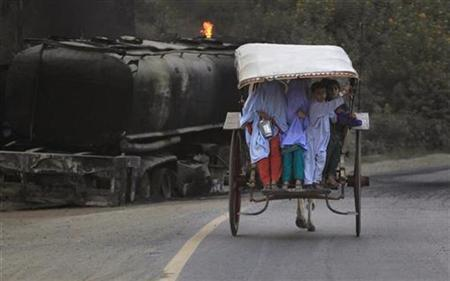 Residents on a horse-led cart past burnt fuel tankers meant for NATO troops, which was set on fire by gunmen on Thursday, along GT road in Nowshera in Pakistan's Khyber-Pakhtunkhwa Province October 10, 2010. REUTERS/Fayaz Aziz