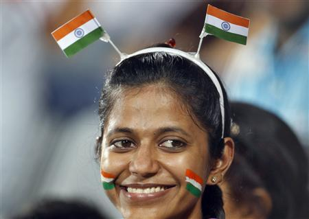An Indian fan smiles as she watches India play England in their men's field hockey semi-final match at the Commonwealth Games in New Delhi October 12, 2010. REUTERS/Danish Ismail