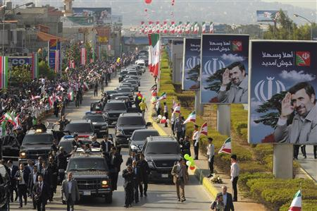 Iranian President Mahmoud Ahmadinejad's convoy escorts him as he waves his hand greeting Lebanese Hezbollah supporters from the open roof of his car upon his arrival at the main airport road in Beirut, October 13, 2010. REUTERS/ Hassan Abdallah