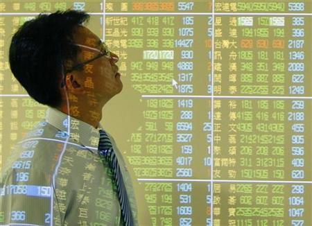 A man walks past a display showing stock market prices inside a bank in Taipei August 31, 2010. REUTERS/Nicky Loh