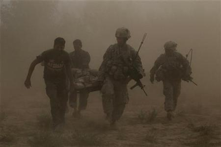 U.S. Army soldiers (R) and Afghan National Army troops carry a wounded U.S. soldier through a dust cloud to a medevac helicopter after his ankle was badly broken by a roadside bomb in southern Afghanistan's Kandahar province, October 13, 2010. REUTERS/Finbarr O'Reilly
