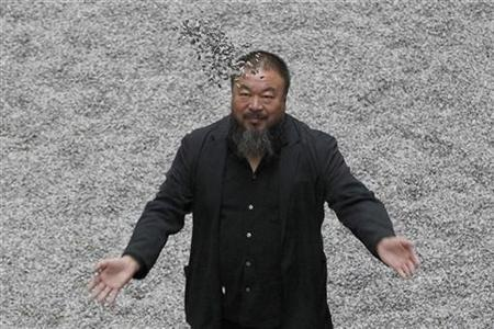 Chinese artist Ai Weiwei throws porcelain sunflower seeds into the air as he poses for a photograph with his new installation entitled 'Sunflower Seeds', at its unveiling in the Turbine Hall at the Tate Modern gallery October 11, 2010. REUTERS/Stefan Wermuth