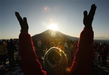 A man raises his hands and shouts ''banzai'' as he and others gather to watch the sunrise over Mount Fuji, which is known locally as ''Diamond Fuji'', from atop Ryugatake mountain in Fujikawaguchiko town, southwest of Tokyo January 1, 2010. REUTERS/Yuriko Nakao