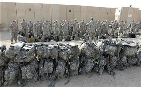 U.S. soldiers of the 1st Battalion, 116th Infantry Regiment, wait to load their luggage as they prepare to pull out from Iraq and leave for Kuwait from Tallil Air Base near Nassiriya, 300 km (185 miles) southeast of Baghdad, August 15, 2010. REUTERS/Thaier al-Sudani
